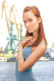 Beautiful lady in the merchant seaport. A beautiful girl on the background of cranes commercial port Stock Photos