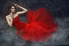 Beautiful lady in nrigh scarlet fishtail dress and vintage necklace sitting in the dry woods covered with smoke royalty free stock images