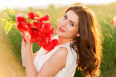Beautiful lady over Sky and Sunset in the field holding a poppies bouquet, smiling Stock Photo