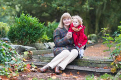 Beautiful lady playing with cute toddler girl on stone Royalty Free Stock Photo