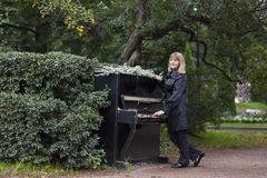 Beautiful lady playing piano in an autumn park Stock Photo