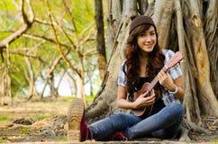 Lady musician. Beautiful lady playing ukulele under  a tree Stock Photos