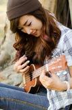 Lady musician. Beautiful lady playing ukulele under  a tree Royalty Free Stock Image