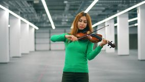 Beautiful lady is playing the violin in an empty hall. 4K stock footage