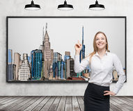 A beautiful lady is pointing out the picture of New York City on the wall. Wooden floor, concrete wall and three black ceiling lig Royalty Free Stock Photography