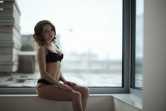 Beautiful lady posing by the window Royalty Free Stock Images