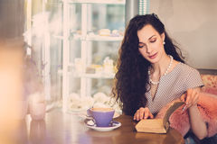 Beautiful lady reading novel in a cafe Royalty Free Stock Photos