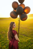 Beautiful lady in red dress with black balloons at sunset Royalty Free Stock Photo