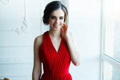 Beautiful lady in red dress with an evening make-up. Portrait of Beautiful Sensual smilyng Woman in Fashion Red Dress. Christmas Sales and Shopping concept Royalty Free Stock Photo