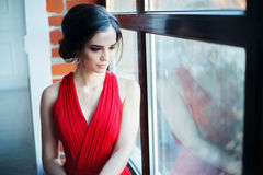 Beautiful lady in red dress with an evening make-up Stock Images
