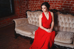 Beautiful lady in red dress with an evening make-up Stock Image