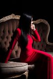 Beautiful lady in red dress on luxury sofa Stock Images