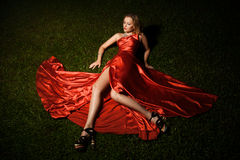 Beautiful Lady In Red Dress Lying On Grass Stock Photos