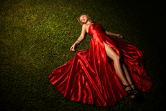 Beautiful Lady In Red Dress Lying On Grass Stock Images