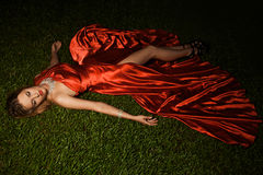 Beautiful Lady In Red Dress Lying On Grass. Beautiful Lady In Red Dress Lying On Green Grass Stock Photo