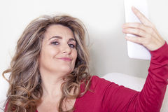 Beautiful lady with red dress takes a selfie. In her home Royalty Free Stock Images