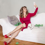 Beautiful lady with red dress takes a selfie. With her kitten Stock Photography