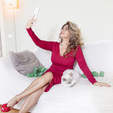 Beautiful lady with red dress takes a selfie. With her kitten Royalty Free Stock Image