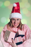Beautiful lady in red Santa hat holding pink gift Royalty Free Stock Photos