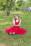 Lady in red dress. Beautiful lady in red are sittiing on green grass Royalty Free Stock Images