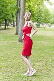 Lady in red dress. Beautiful lady in red are standing at the summer day Royalty Free Stock Photo