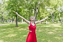 Lady in red dress. Beautiful lady in red are standing at summer day with upward hands Royalty Free Stock Image