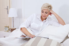 Beautiful lady relaxing in bed at the morning. Royalty Free Stock Image