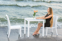 A beautiful lady resting on a blue sea background. A happy girl in a black dress. A set of table and chairs on a beach. stock photo