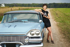 Beautiful lady with a retro camera. Retro woman posing with a retro camera standing near a retro car outdoors Stock Photography