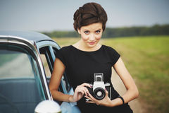 Beautiful lady with a retro camera. Retro woman posing with a retro camera standing near a retro car outdoors Stock Photos