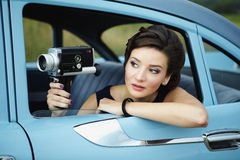 Beautiful lady with a retro movie camera. Retro woman posing with a retro movie camera sitting in  a retro car outdoors Stock Photos