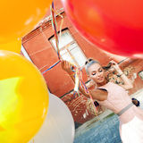 Beautiful lady in retro outfit holding a bunch of balloons betwe Royalty Free Stock Image