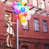 Beautiful lady in retro outfit holding a bunch of balloons betwe Royalty Free Stock Images