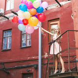 Beautiful lady in retro outfit holding a bunch of balloons betwe Royalty Free Stock Photos