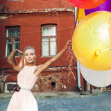 Beautiful lady in retro outfit holding a bunch of balloons betwe Stock Photography