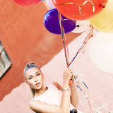 Beautiful lady in retro outfit holding a bunch of balloons betwe Stock Image