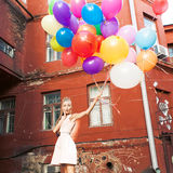 Beautiful lady in retro outfit holding a bunch of balloons betwe Stock Images