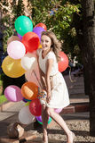 Beautiful lady in retro outfit holding a bunch of balloons in ci Stock Image