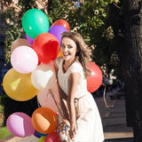 Beautiful lady in retro outfit holding a bunch of balloons in ci Stock Images