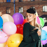 Beautiful lady in retro outfit holding a bunch of balloons in ci Royalty Free Stock Images