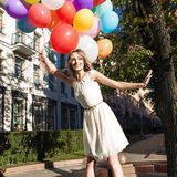 Beautiful lady in retro outfit holding a bunch of balloons in ci Stock Photo