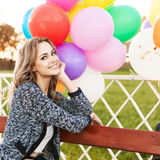 Beautiful lady in retro outfit holding a bunch of balloons in ci Royalty Free Stock Photos