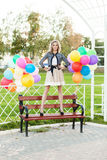 Beautiful lady in retro outfit holding a bunch of balloons in ci Royalty Free Stock Image