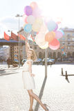 Beautiful lady in retro outfit holding a bunch of balloons on th Stock Photo