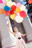 Beautiful lady in retro outfit holding a bunch of balloons on th Royalty Free Stock Photos