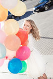 Beautiful lady in retro outfit holding a bunch of balloons on th Royalty Free Stock Photo
