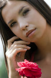 Beautiful lady with rose. Portrait of the beautiful young woman holding red rose Royalty Free Stock Image