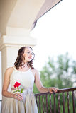 Beautiful lady with a rose. Pretty sad Woman with beautiful blue eyes and a red rose looking out Royalty Free Stock Photography