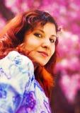 Beautiful lady on sakura blossom background, pink flowers, Orange Feathered earring. Royalty Free Stock Image