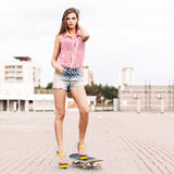 Beautiful lady in short jeans shorts stands on skateboard Royalty Free Stock Photography